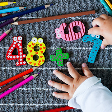 little hands playing with number blocks and pencils