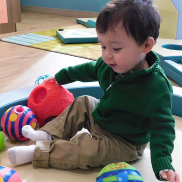little boy sitting on classroom rug playing with toys