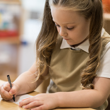 girl writing on paper with crayon