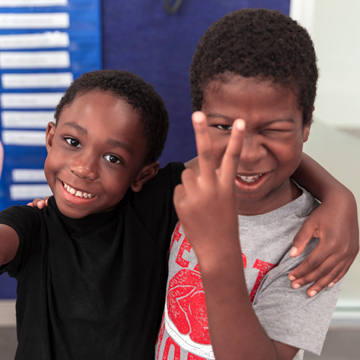 two boys smiling and giving the peace sign